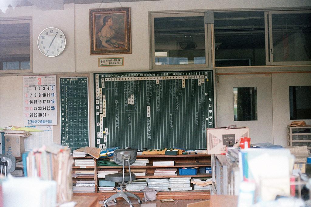 """楢葉北小学校 行事曆 福島 竜田駅 2015/08/06 楢葉北小学校的職員室,本來想說要偷偷爬進去,但是門窗都很謹慎的上鎖了,只好靠著窗戶看裡面的狀況。我看到牆面上的行事曆,看到一些畢業預演的事宜。左邊的月曆則是停留在 2011 年 3 月那頁。上面的時鐘還是繼續在運作,只是時間不準了,應該過沒多久也會停止。就這樣一切都會停止下來 ...  Nikon FM2 / 50mm Kodak ColorPlus ISO200  <a href=""""http://blog.toomore.net/2015/08/blog-post.html"""" rel=""""noreferrer nofollow"""">blog.toomore.net/2015/08/blog-post.html</a> Photo by Toomore"""