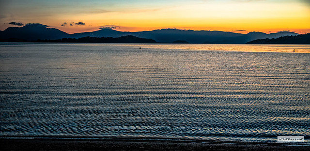 Panoramic view of sunrise over the hills and islands of Loch Lomond.