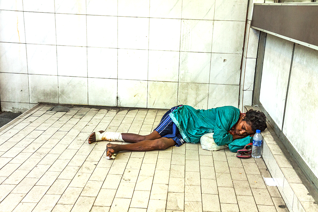 Woman on ground outside currency exchange business--Johor Bahru