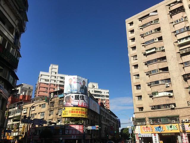上班路上看到覺得很衝突的廣告看板:上面是強調居住正義的候選人,下面是號稱百萬裝潢每坪五字頭的建案廣告。