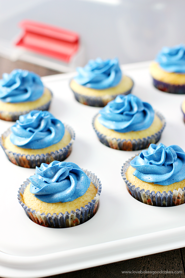 Cupcakes with blue frosting in a cupcake pan.