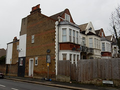 A terrace of tall, narrow houses viewed end-on.  A sign for Broughton Road can be seen on the side road that marks the end of the terrace.  Each house has two fairly high storeys, each with a bay window, and a smaller peaked roof space with another window in.