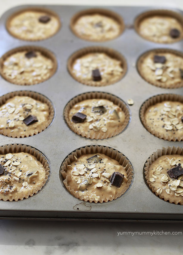 Healthy peanut butter oatmeal muffin batter topped with oats, chia seeds, and chocolate chunks.