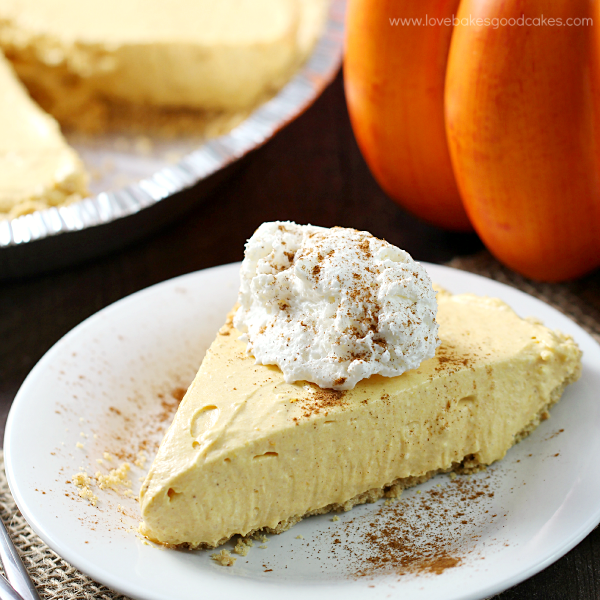 No-Bake Pumpkin Spice Cheesecake on a plate with whipped cream up close.