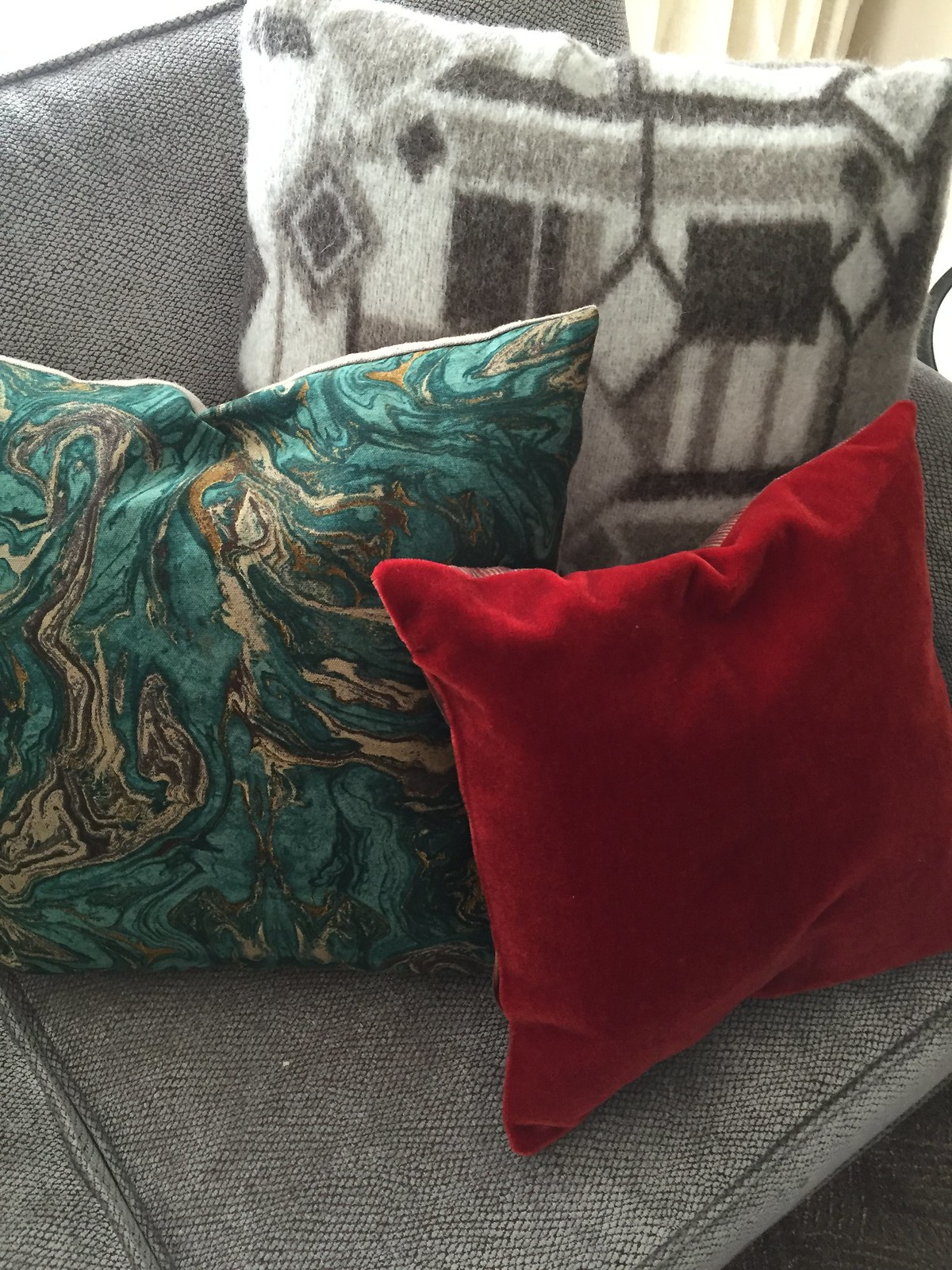 Red velvet cushion mixed in with everyday cushions for a Christmas look