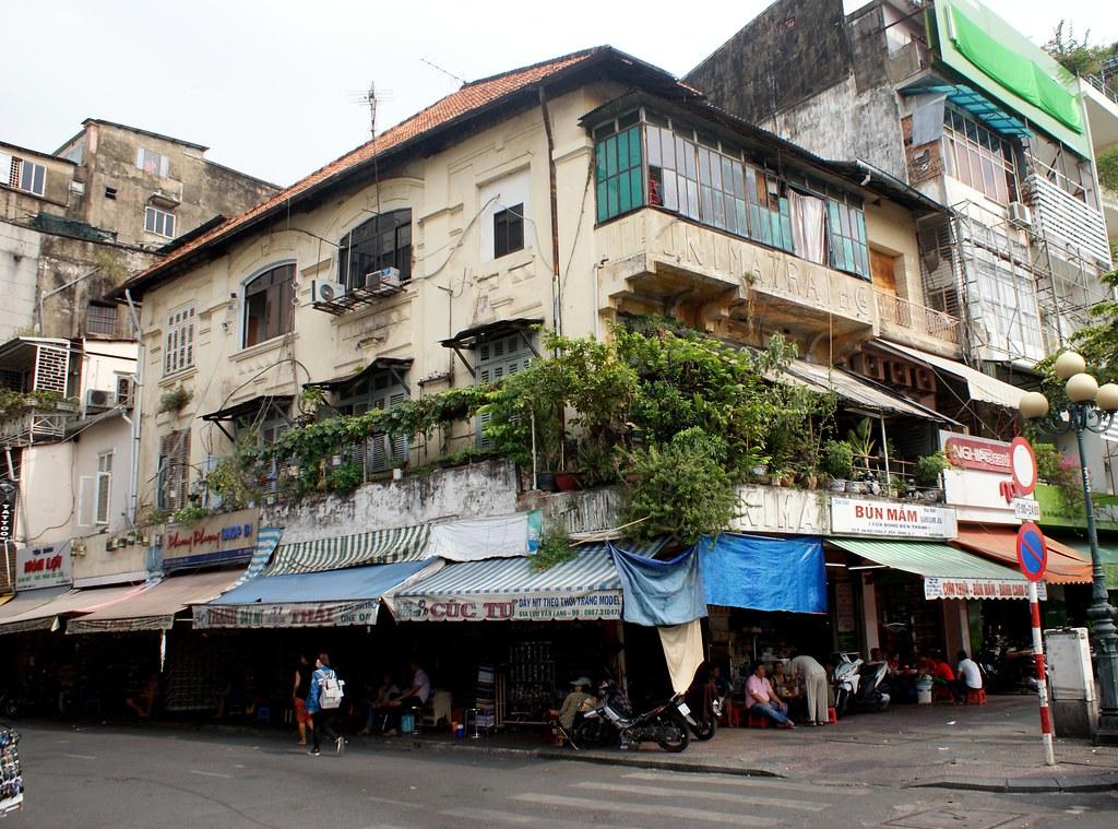 Batiment de Saigon avec une végétation luxuriante, des enseignes et des ajouts sur la façade donnant un aspect joliment bordélique.