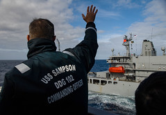 Cmdr. Timothy Labenz, commanding officer of USS Sampson (DDG 102), hails HMNZS Endeavour (A11) before their replenishment-at-sea. (U.S. Navy/PO2 Bryan Jackson)
