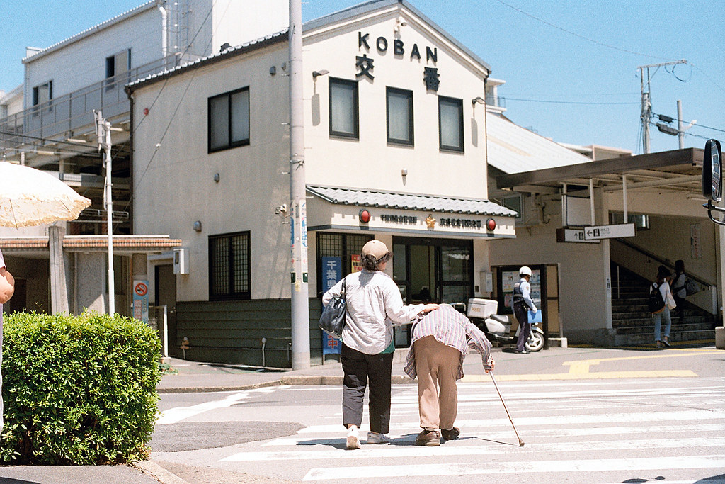 """京成佐倉駅 Koban Keisei-Sakura 2015/08/05 後來在 #京成佐倉 車站附近看到的畫面。本來是站在很遠的地方拍後面的交番 #Koban ,因為日本各地的交番都很特別。退到一個路口後面遠遠的看到阿婆要走到車站,我都盡量避免拍攝正面,因此等到她們走到我想要的畫面中才拍下來!  還好那時候我沒有很堅持用大光圈,要不然有可能會對焦失敗,後來想到這樣的問題,不要太堅持什麼,把一個完整的畫面清楚的記錄下來才比較重要,否則回來之後都是失焦的作品,就完全沒辦法表達當時的狀況。  Nikon FM2 / 50mm Kodak ColorPlus ISO200  <a href=""""http://blog.toomore.net/2015/08/blog-post.html"""" rel=""""noreferrer nofollow"""">blog.toomore.net/2015/08/blog-post.html</a> Photo by Toomore"""