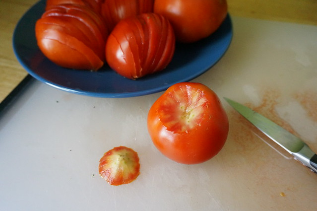 Coring the red tomatoes: a freshly cored tomato sits on a cutting board in front of a plate of cored and sliced tomatoes. The core, removed, sits next to it.