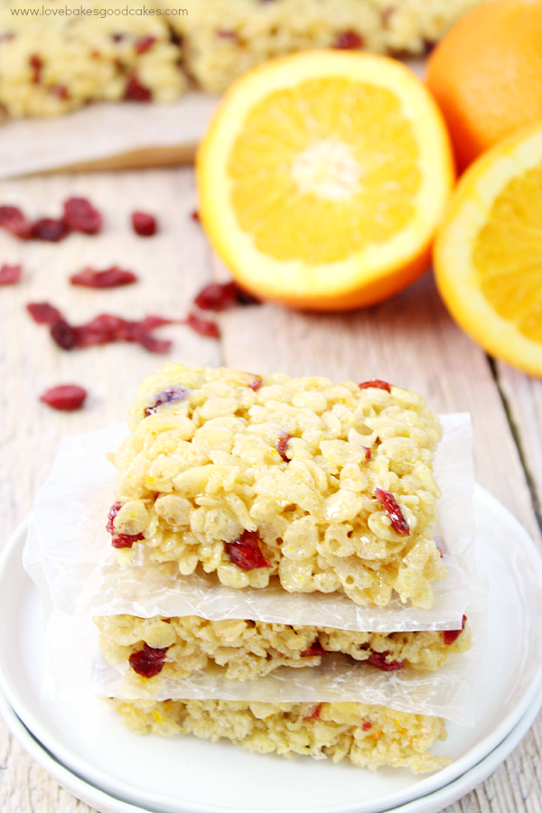 Cranberry Orange Crispy Treats stacked on a plate with oranges.