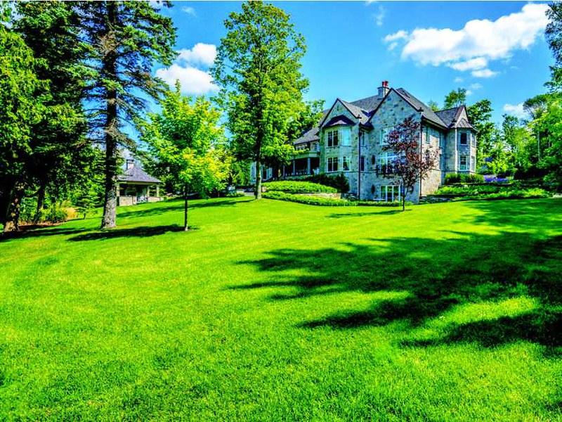 Зелёная лужайка у каменного дома в Канаде
