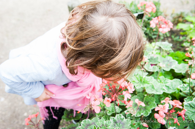 Visiting Paris with Kids and Aggie smelling the flowers at the Jardin de Plants