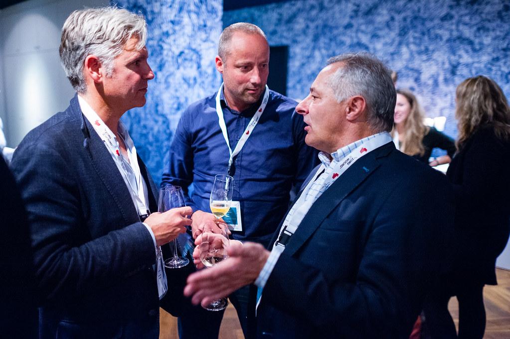 Tafelgast dr. Aernout Somsen, dagvoorzitter drs. Tom van 't Hek en een zaalgast zoeken elkaar op tijdens de borrel