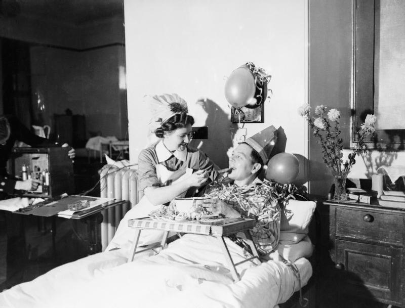 A nurse feeds a patient with a spoonful of Christmas pudding at a naval hospital at Kingseat in Scotland, December 1941