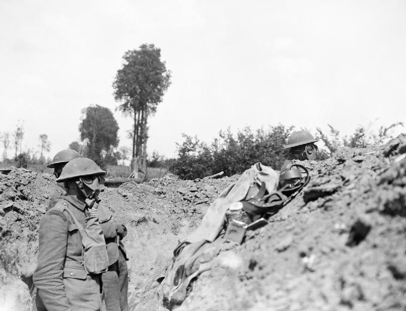 Men of the 12th Royal Scots wear respirators during a gas attack on a front line trench, Meteren.
