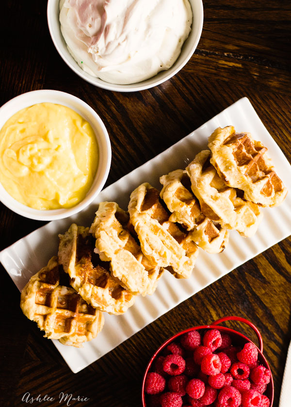 traditional liege waffles topped with a homemade lemon curd, fresh whipped cream and raspberries. a bright, sweet treat, with the perfect amount of bright tart lemon