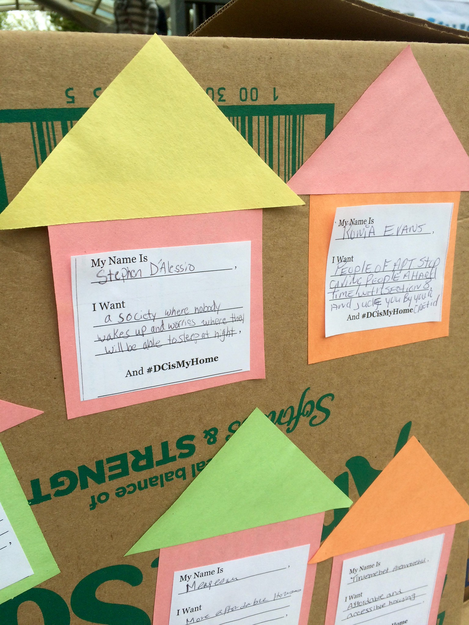 A cardboard box covered with colored paper cut into the shape of houses. People have written their dreams for the future of D.C. on the paper houses.