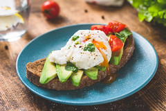 Delicious sandwich with poached egg and avocado