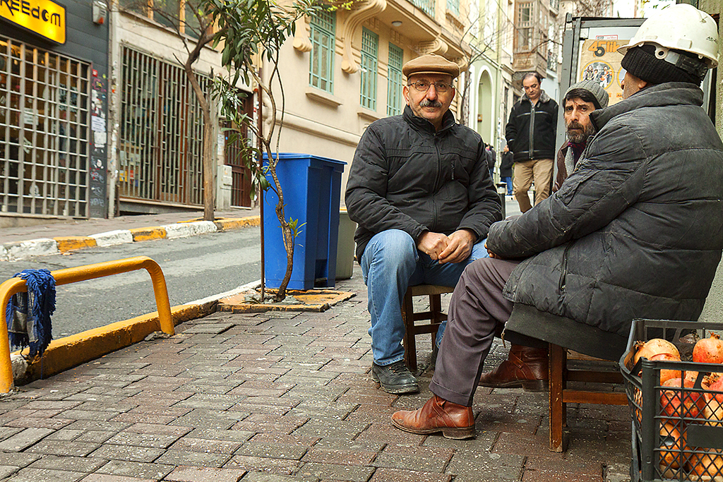 Men at low table outside tiny eatery--Istanbul