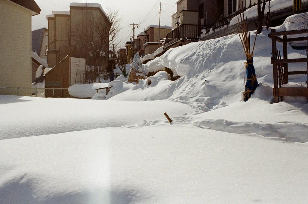 小樽 Otaru, Japan / Kodak ColorPlus / Nikon FM2 自然堆砌起來的雪真的好漂亮,有一點點雪高的感覺,但是這雪很軟而且會有假象的陷阱。  在前一個路口,我偷懶想要越過一個斜坡往上走,踩在一個想是這樣個雪坡上,結果整個掉下去半個人深。  地下是空的!  後來我趕快抓旁邊的曬衣桿(不知道哪裡冒出來的)撐起來,狼狽的爬上斜坡,但是褲子、鞋子全部都積雪、融雪濕透。  然後我就嚇到,下次不能夠這樣在雪地裡亂爬。  Nikon FM2 Nikon AI AF Nikkor 35mm F/2D Kodak ColorPlus ISO200 8268-0037 2016/02/02 Photo by Toomore