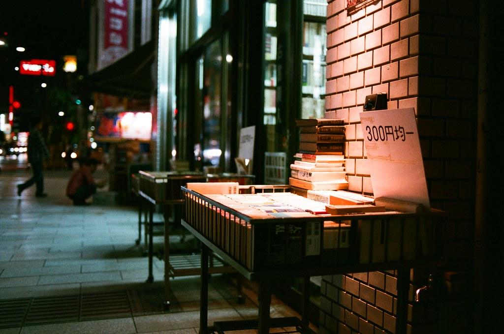 神保町 東京 Tokyo 2015/10/03 東京神保町,很有名的舊書攤街,這是我第二個晚上來到這裡找書。第一次來的時候其實已經有看到一本候選的書,但想說那時候才剛到東京,還有一點時間可以找看看有沒有更適合的書。後來逛了好多地方都沒有比原本的適合,於是決定再回到神保町、再回到原來的書店,把那本書帶走!  那是一本手繪日本皇居御所內的草木植物的圖鑑,因為都是手繪,非常特別的一本書《皇居東御苑草木帖》  Nikon FM2 Nikon AI AF Nikkor 35mm F/2D AGFA VISTAPlus ISO400 1001-0005 Photo by Toomore