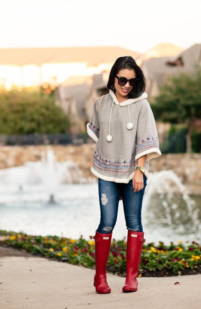 cute & little blog | petite fashion | knit pom pom poncho, distressed denim, red hunter tour boots | fall outfit