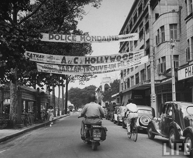 Typical street in Saigon, with cyclists and Tarzan movie advertising at local theatre.