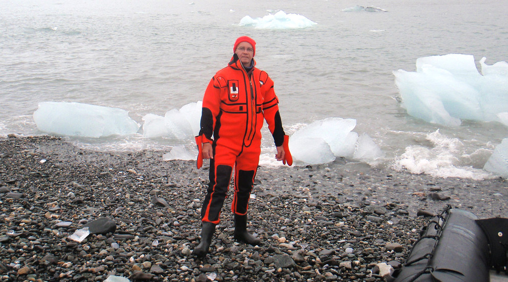 Dr Philippe Blondel, standing on the Svalbard coast, wears an orange protective suit against the cold of the Arctic Ocean.