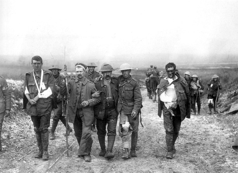 A German prisoner helps British wounded make their way to a dressing station near Bernafay Wood following fighting on Bazentin Ridge, 19 July 1916, during the Battle of the Somme.