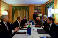 U.S. Secretary of State John Kerry, Russian Foreign Minister Sergey Lavrov, and their respective aides sit across from one another on December 2, 2016, at the Parco dei Principe Hotel in Rome, Italy, before a bilateral meeting on the sidelines of an an Italian-hosted multinational meeting focused on Mediterranean issues. [State Department photo/ Public Domain]