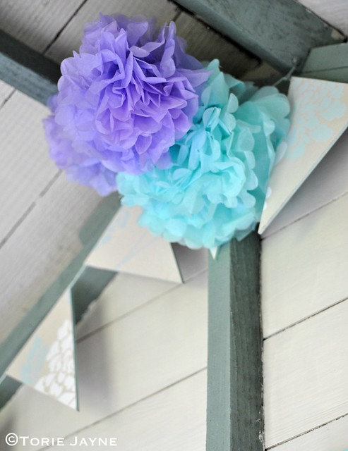 Paper pom pom flowers hanging in my summerhouse