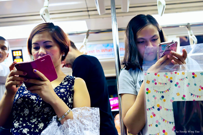 Commuters And Their Mobile Phones On The Train