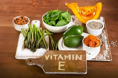 Foods containing vitamin E on a wooden board.