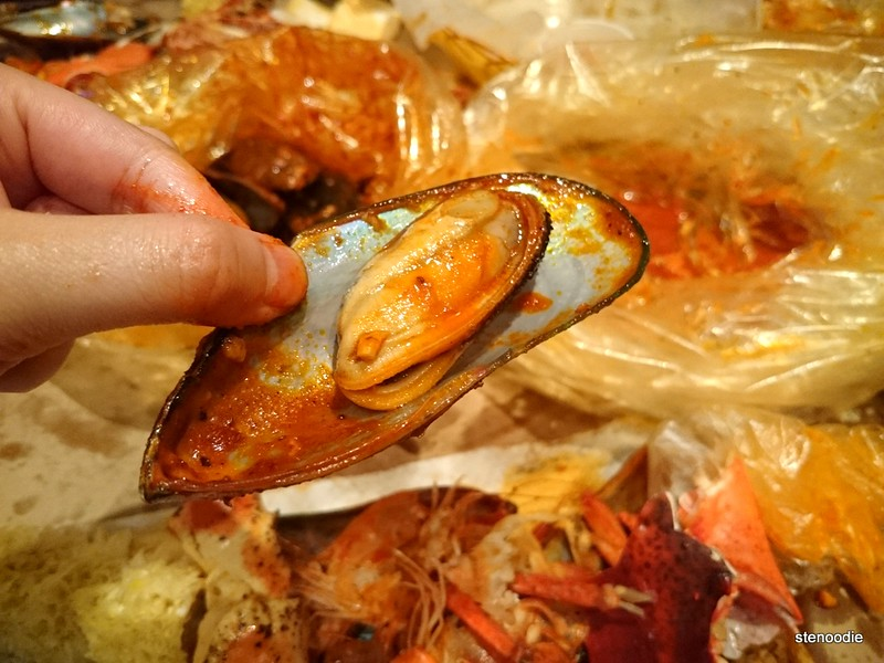hand holding mussel in seafood boil