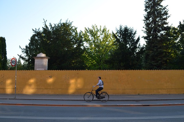 bicyclist against yellow wall of Assistens Kirkegård cemetary