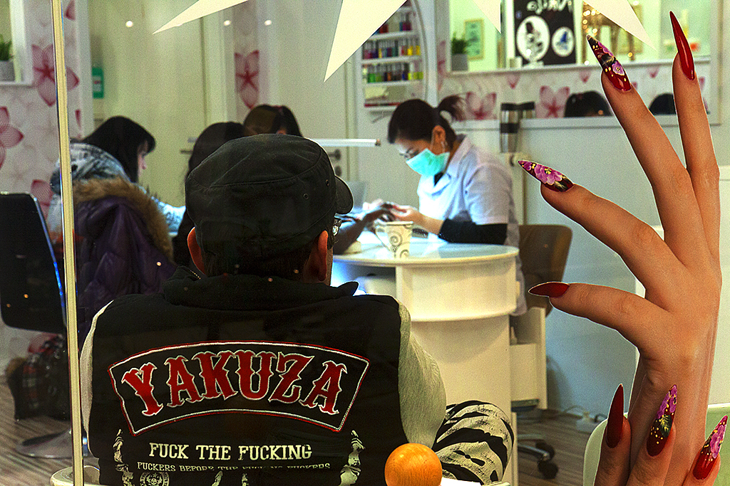 Man wearing YAKUZA jacket inside Vietnamese nail salon--Leipzig