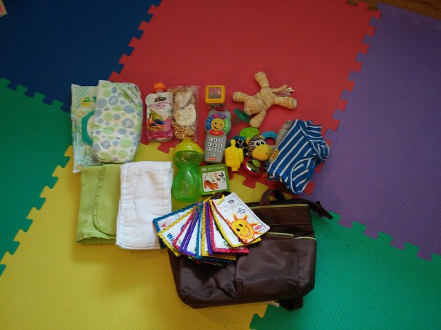 A diaper bag and its contents, spread out for display. Wubanubs, yogurts, books, and more.