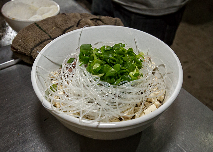 Glass noodles, scallions, and flat bread in a bowl.