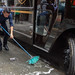 New York City Street Scenes - Man Washing a Sidewalk with a Broom Next to a UPS Truck by Steven Pisano