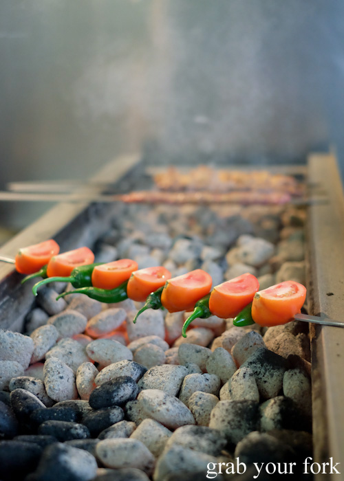 Tomato and green chilli shish kebabs cooking over charcoal at New Star Kebasb, Auburn