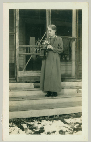 Woman on the steps of a screened-in porch