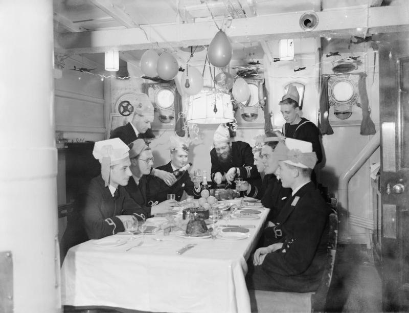 In the ward room that has been decorated with balloons and streamers, the First Lieutenant carves the joint during Christmas celebrations on board HMS WESTMINSTER at Rosyth