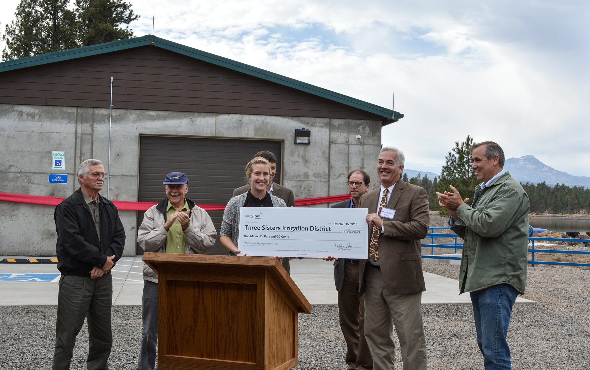 Lindsey Hardy of Energy Trust presents a check for $1 million toward the plant construction and operations for TSID manager Marc Thalacker during observances at Watson Reservoir last week.  Also featured in the photo (l to r) Alan Meyer, board member, Energy Trust of Oregon; John Reynolds, board member, Energy Trust of Oregon; Jed Jorgensen, renewables program manager, Energy Trust of Oregon (back); Peter West, energy programs manager, Energy Trust of Oregon (back) and Oregon Sen. Jeff Merkley, - Photo Credit: Energy Trust of Oregon