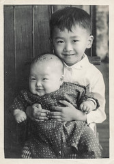 Little Chinese boy holding a smiling baby