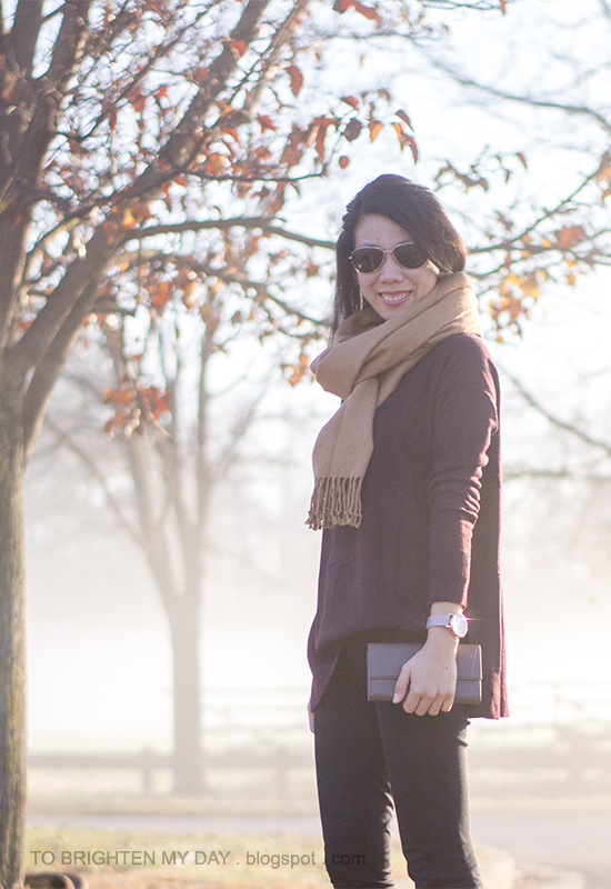 camel scarf, plum tunic sweater, taupe clutch, black pants