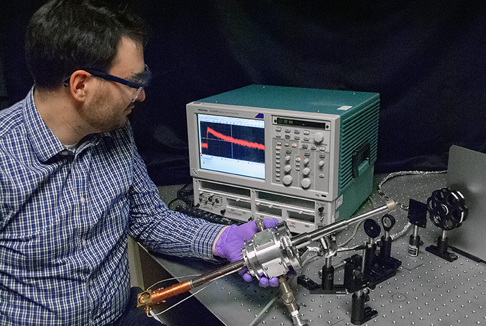 Andrew Fidler of Los Alamos National Laboratory examines an ultrafast photodetector used to measure quantum dot carrier multiplication in real time.