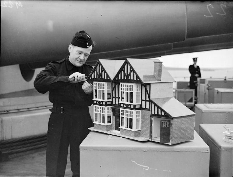 On the foc'sle of a battleship, in the shadow of the guns, a Royal Marine, J Lynch of Newport, Monmouthshire is putting the finishing touches to a large dolls house, complete with furniture, 1943